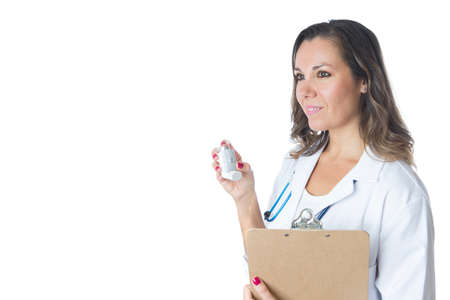 Friendly female doctor is holding a pressurized cartridge inhaler and a clipboard - Isolated on a white background Stock Photo