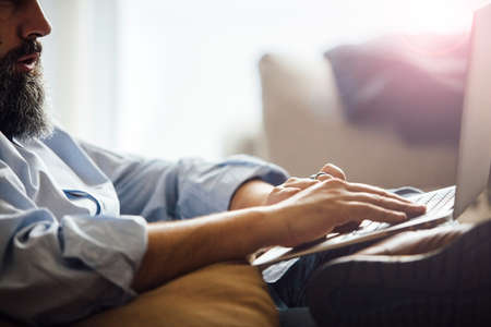 Side view of unrecognizable bearded man typing on laptop.Backlit. Stock Photo