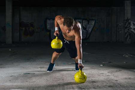 and the horizontal man: Man doing exercise with big dumbbells. Horizontal indoors shot Stock Photo