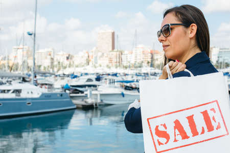 Young beautiful female in sunglasses standing on quay with white shopping bag.
