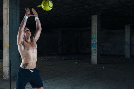 and the horizontal man: Young strong man throwing weight up while standing in abandoned building. Horizontal indoor shot