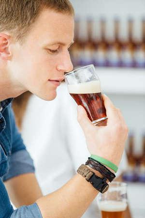 Side view of blonde man smelling dark craft beer