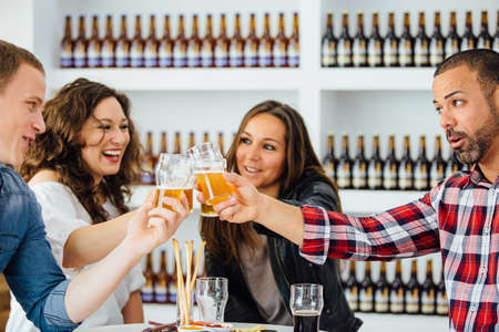 Two menn and women toasting with glasses of beer Stock Photo