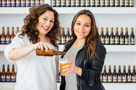 Portrait of two attractive women pouring beer from bottle and looking at camera Stock Photo