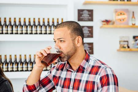 Portrait of adult man with beard drinking dark beer