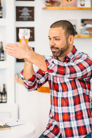 Portrait of smiling man covering glass of beer with hand and looking at it