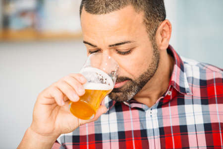 Close-up of bearded man smelling light craft beer in glass