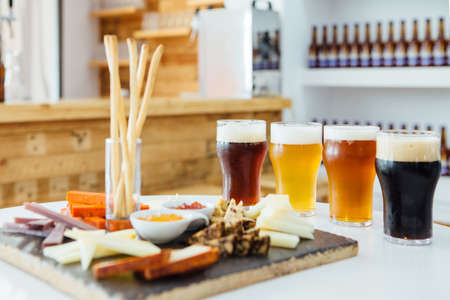 View on table with snack board and four glasses of different craft beer Imagens - 68754303