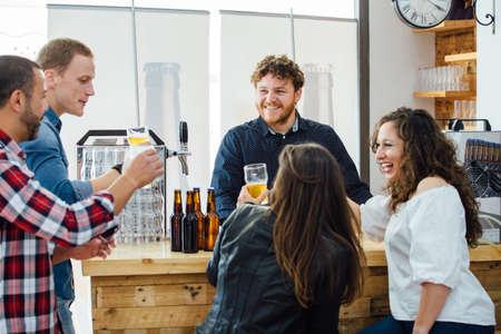 compañía de dos mujeres y tres hombres tomando una cerveza artesanal en conjunto