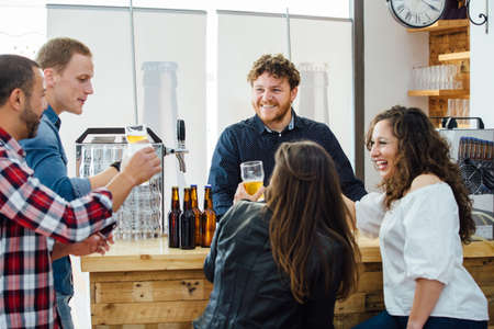 company of two women and three men drinking craft beer together Standard-Bild