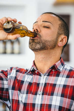 bottled beer: Close-up of bearded man drinking bottled beer Stock Photo