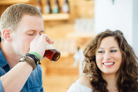 near beer: Portrait of blond man drinking craft beer with eyes closed.Smiling brunette near him.