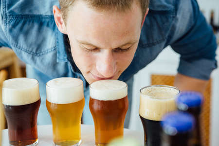 Close-up of blond man smelling different craft beer with froth Stock Photo