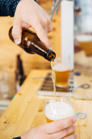 Close-up of unrecognizable man pouring bottled beer in glass