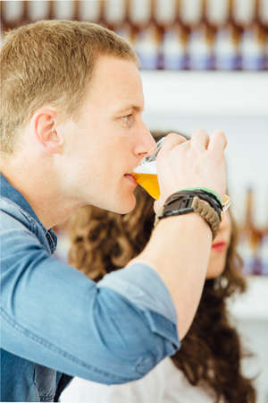 Side view of handsome blond man drinking light craft beer Stock Photo
