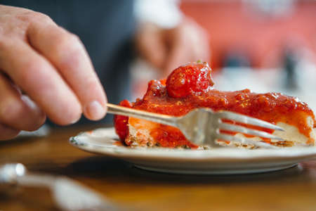 Close up of unrecognizable person eating straweberry cake with fork Stock Photo