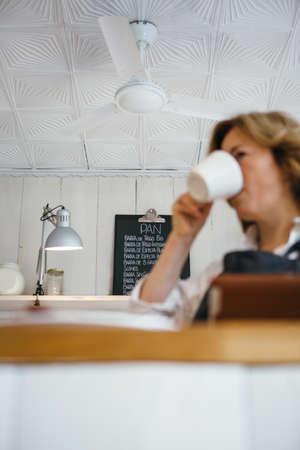 Unfocused woman drinking coffee against of board with menu