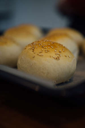 Close-up of tasty crunchy bun with sesame on oven tray Stock Photo