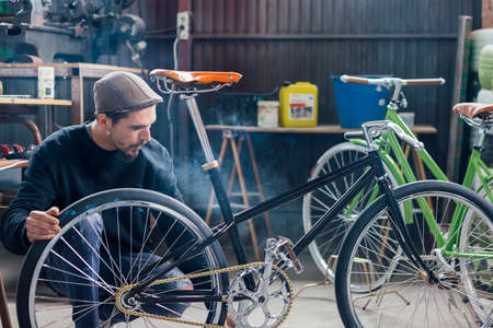 disassemble: Bearded man looking at his new bicycle while smoking at workplace Stock Photo