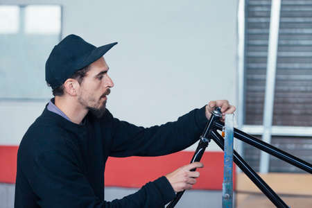 Bearded man working with metal bars Stock Photo