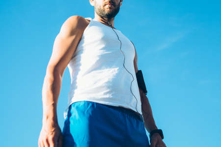 bearded wires: Horizontal crop outdoors shot of sportsman with earphones against clear sky.