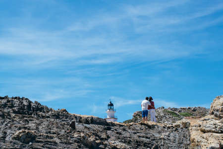 Back view of a couple standing on coastal stone and looking at lighthouse. Stock Photo