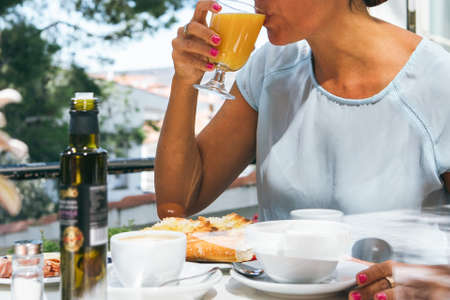 Horizontal indoors shot of unrecognizable adult woman drinking juice breakfasting in cafe.