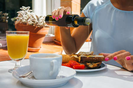 인식 할 수없는 여자 토스트 한 카페에서 아침 식사에 기름을 붓는. 스톡 콘텐츠