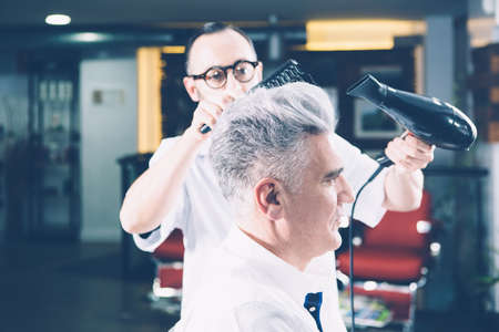 Side view of professional hairdresser working with drier on client hairstyle.
