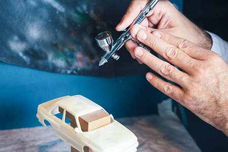 sportcar: Hands of unrecognizable man using airbrush for painting handcrafted miniature auto.