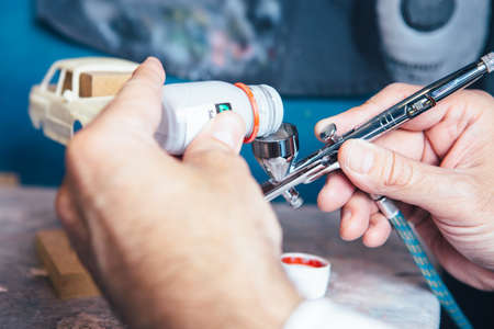 sportcar: Unrecognizable person pouring paint to airbrush for slot car painting. Stock Photo