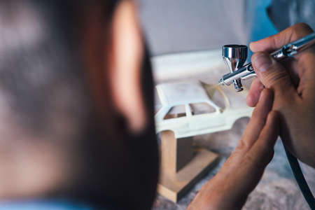 Horizontal close-up shot of person working with aerograph painting miniature auto.
