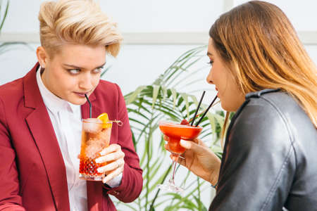 Beautiful girlfriends drinking cocktails while sitting at table in cafe and looking at each other. Stock Photo