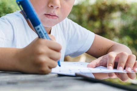 큰 파란색 펜을 들고 뒤뜰에 테이블에 앉아 메모장에서 작성 소년의 자르기 샷.