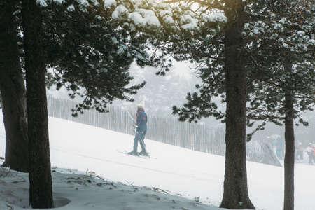Skifahrer benutzt den Skiaufzug, um durch eine Steigung zum Gipfel auf einer Schneespur transportiert zu werden, um zu beginnen, Ski zu fahren