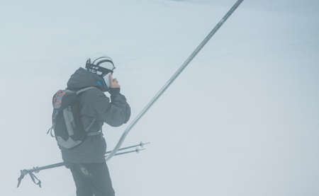 Skier is using a mobile phone while is using the ski lift to be transported by a slope to the top of on a snow track to start to ski on a foggy day at the ski resort