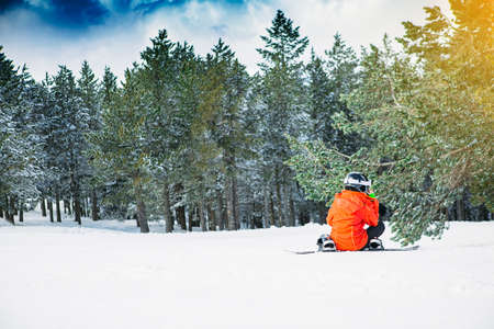 Young woman snowboarder stopped with the snowboard removed on a snowy track to answer the mobile phone Stock Photo