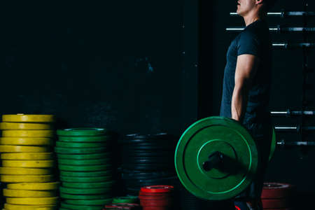 Cropped view of the side view of a young man doing deadlift exercise on a fitness routine at the box gym. Copy space area available Foto de archivo