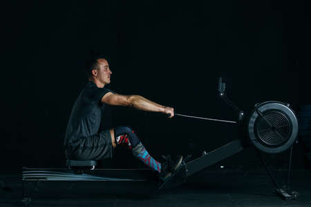 Side view of a young man athlete doing rowing exercise on a fitness routine at the box gym Stock Photo