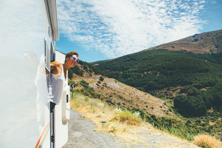 Young woman is looking out the caravan door on a holiday adventure trip. Copy space area available