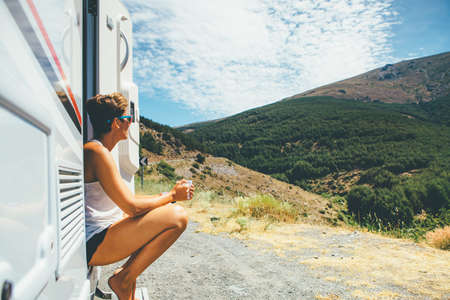 Side view of a young woman is sitting on a caravan step and holding a cup on a holiday adventure trip stop. Copy space area available Stock Photo