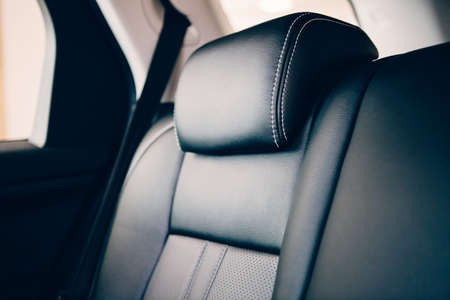 Close up of an elegant car headrest upholstered in black handmade leather