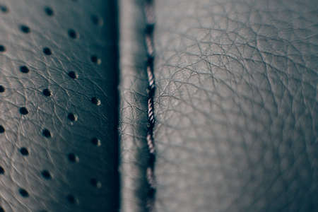 Close up of a detail of the stitches of a car seat in a black handmade leather upholstery. Useful as a background