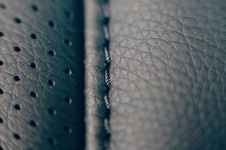 Close-up van een detail van de steken van een autostoel in een zwarte handgemaakte lederen bekleding. Handig als achtergrond Stockfoto