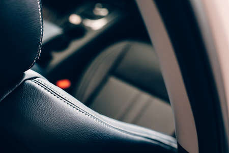 Cropped view of a black leather handmade upholstered seat of an elegant car. Top and back view