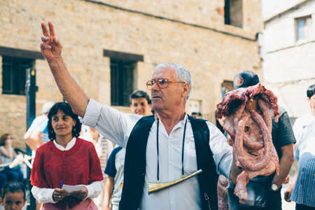 PUERTOMINGALVO, TERUEL, SPAIN - AUGUST 5, 2018: Old man makes a pork meat auction in a medieval fair celebrated in Puertomingalvo, a small town located in the Maestrazgo Cultural Park in the region of Gudar Javalambre, in the province of Teruel, Aragon, S Stock Photo - 133785029