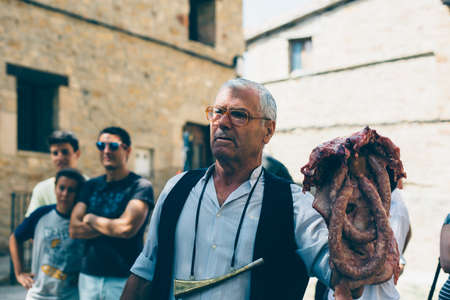 PUERTOMINGALVO, TERUEL, SPAIN - AUGUST 5, 2018: Middle aged man makes a pork meat auction in a medieval fair celebrated in Puertomingalvo, a small town located in the Maestrazgo Cultural Park in the region of Gudar Javalambre, in the province of Teruel, A Editorial