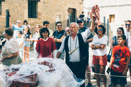 PUERTOMINGALVO, TERUEL, SPAIN - AUGUST 5, 2018: Man makes a pork meat auction in a medieval fair celebrated in Puertomingalvo, a small town located in the Maestrazgo Cultural Park in the region of Gudar Javalambre, in the province of Teruel, Aragon, Spain