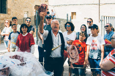 PUERTOMINGALVO, TERUEL, SPAIN - AUGUST 5, 2018: Man is making a pork meat auction in a medieval fair celebrated in Puertomingalvo, a small town located in the Maestrazgo Cultural Park in the region of Gudar Javalambre, in the province of Teruel, Aragon, S Editorial