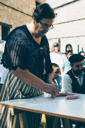 PUERTOMINGALVO, TERUEL, SPAIN - AUGUST 5, 2018: Old woman is making handmade sausage during an exhibition in a medieval fair celebrated in Puertomingalvo, a small town located in the Maestrazgo Cultural Park in the region of Gudar Javalambre, in the provi Editorial